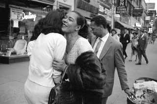 Billie Holiday with Carl Drinkard on Broad Street in New York, receiving a gift from a fan. Jerry Dantzic