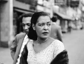 Billie Holiday with Carl Drinkard on Broad Street in New York. Jerry Dantzic