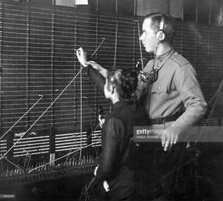 Солдат учит девушку работе на телефонной станции. Большинство телефонисток присоединились к забастовке.