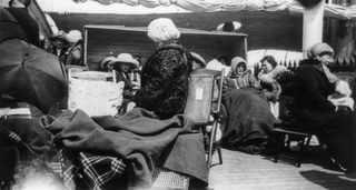 """15 апреля 1912, Спасшиеся пассажиры пытаются согреться на палубе лайнера """"Carparthia"""""""